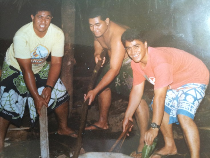 Three friends participate in Samoan coconut husking, a Samoan tradition