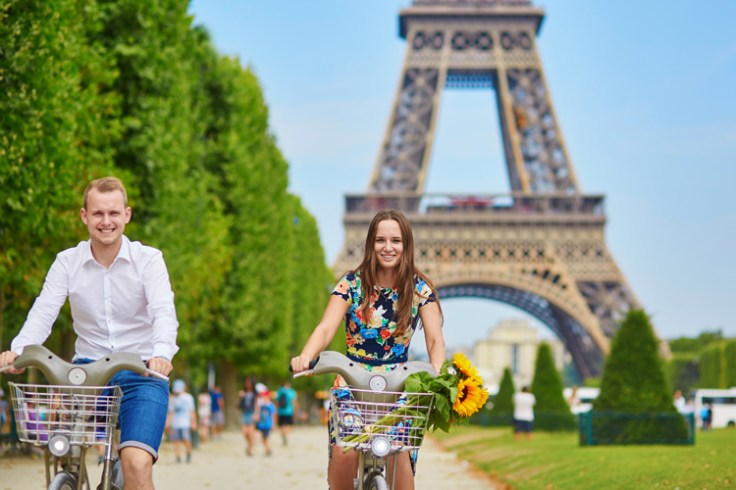 A couple riding bicycles in France.