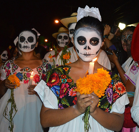 A girl dressed for day of the dead holding a candle