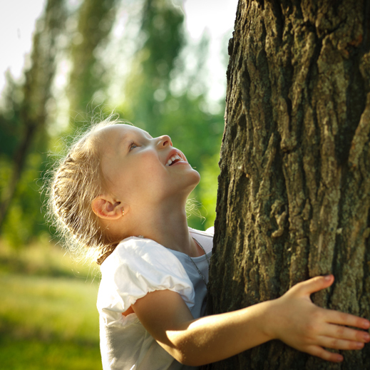 A young girl looking up at a big tree.