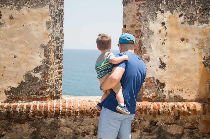 a puerto rican father and son look out onto the ocean.
