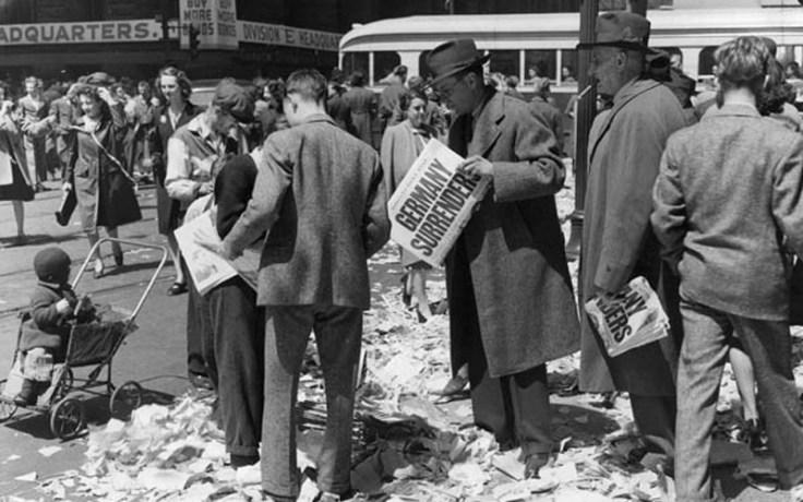 "Men hold newspaper reading ""Germany Surrenders"""