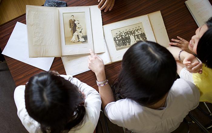 Uma mãe e sua filha trabalham para acrescentar recordações à sua árvore familiar, revendo fotos antigas da família.