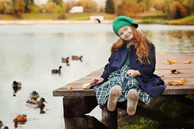 a little irish girl sits on a bridge