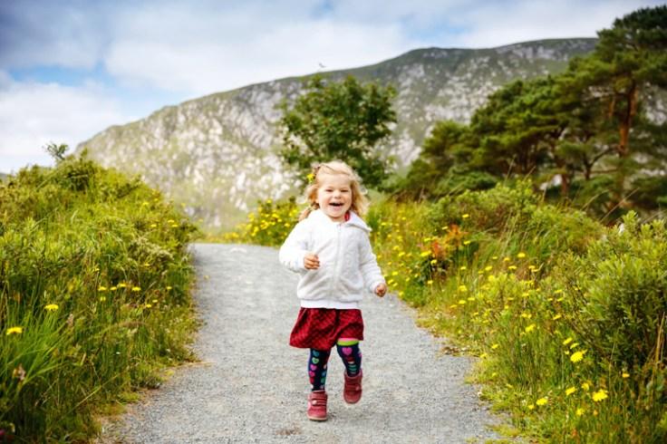 a little irish girl runs down a path.