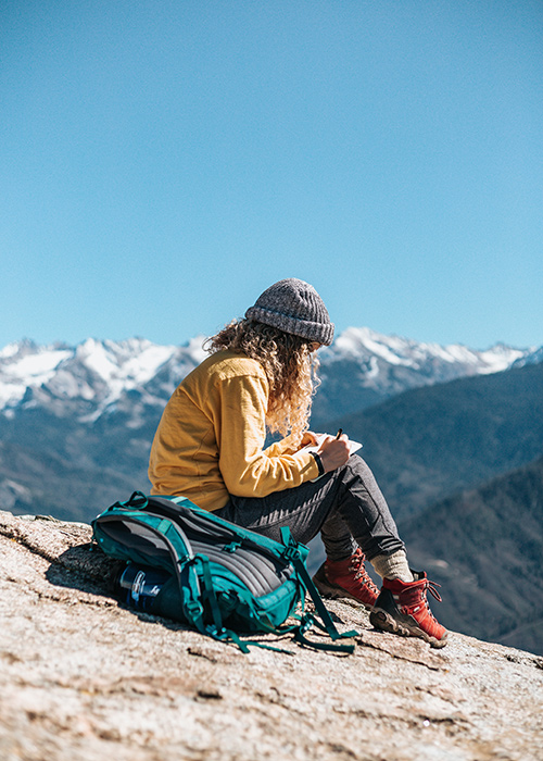 a woman journals on a hike.