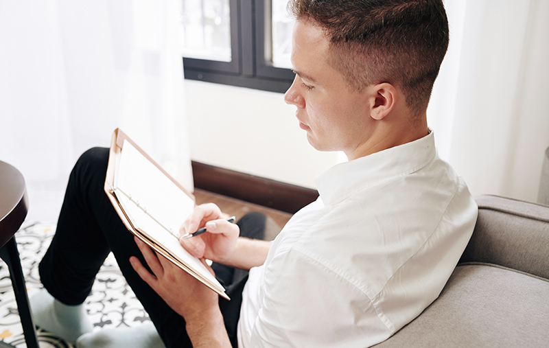 a man begins writing from a journal prompt.