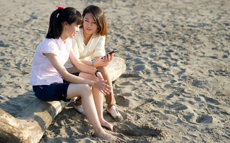 Мать с дочерью сидят на пляже с мобильным телефоном