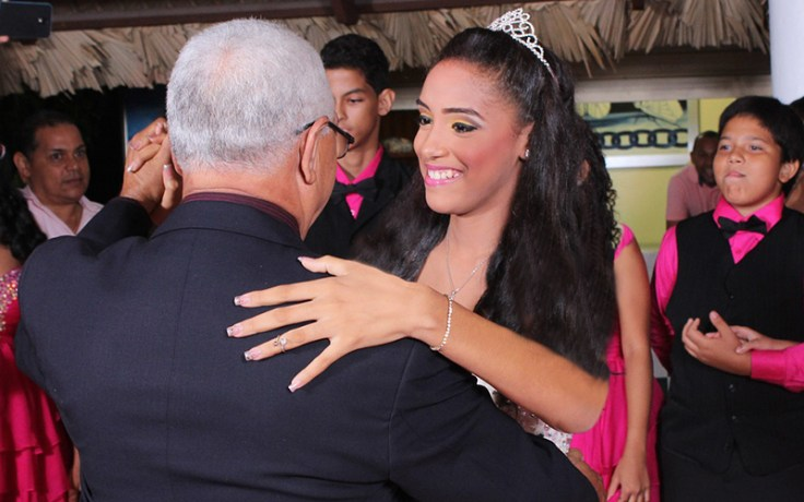 a girl dances with her father at her quinceañera