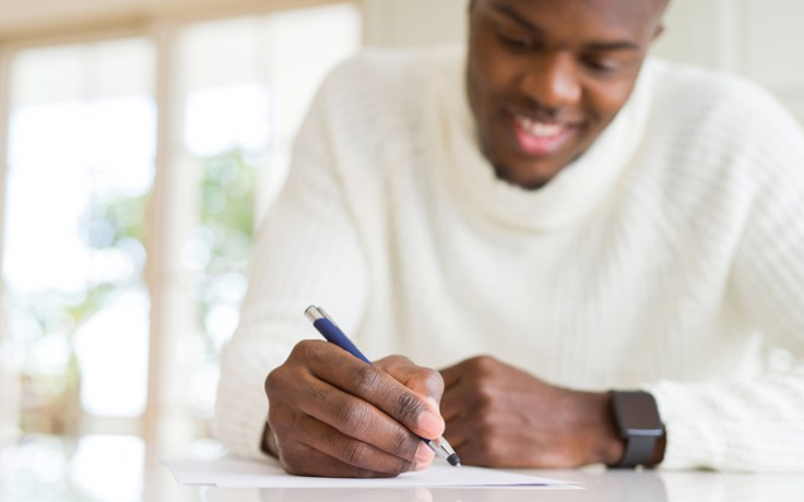 a black man celebrates black history month writes his personal history in a journal