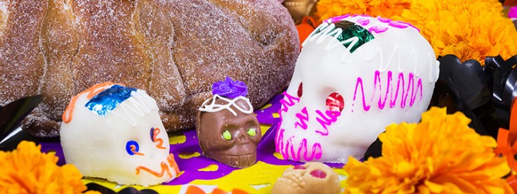 Sugar skulls beside pan de muerto and marigolds