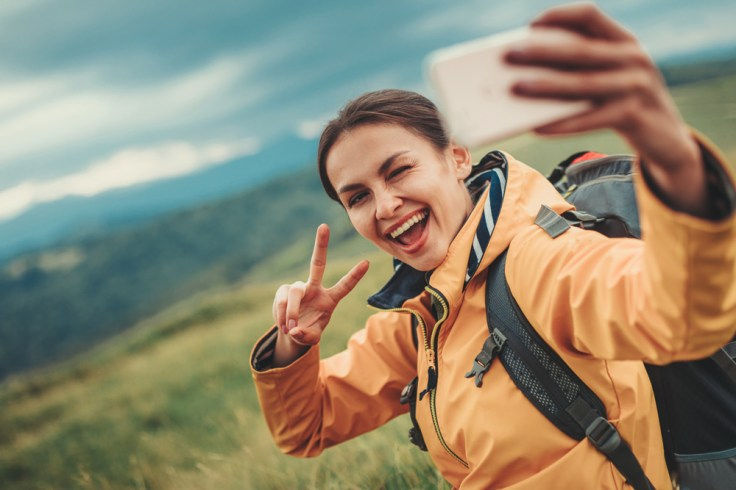 Millennial woman taking selfie with phone