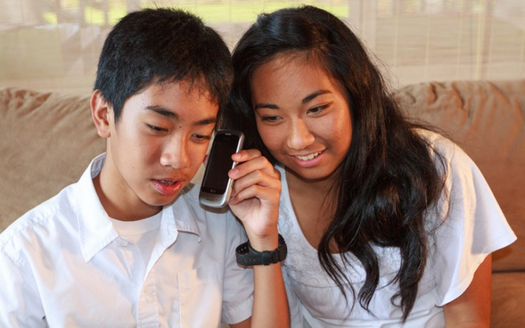 A boy and girl fill out the census via the phone.