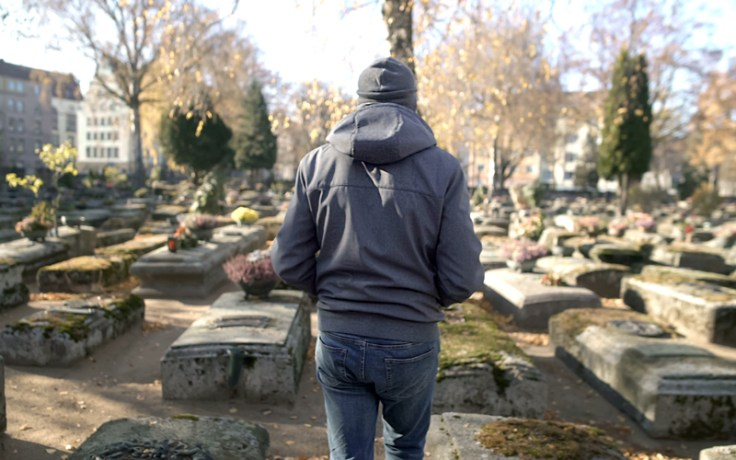 A man walks through a graveyard