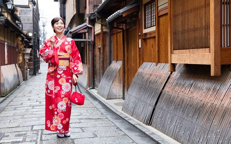 a woman in a japanese kimono walks down a street.