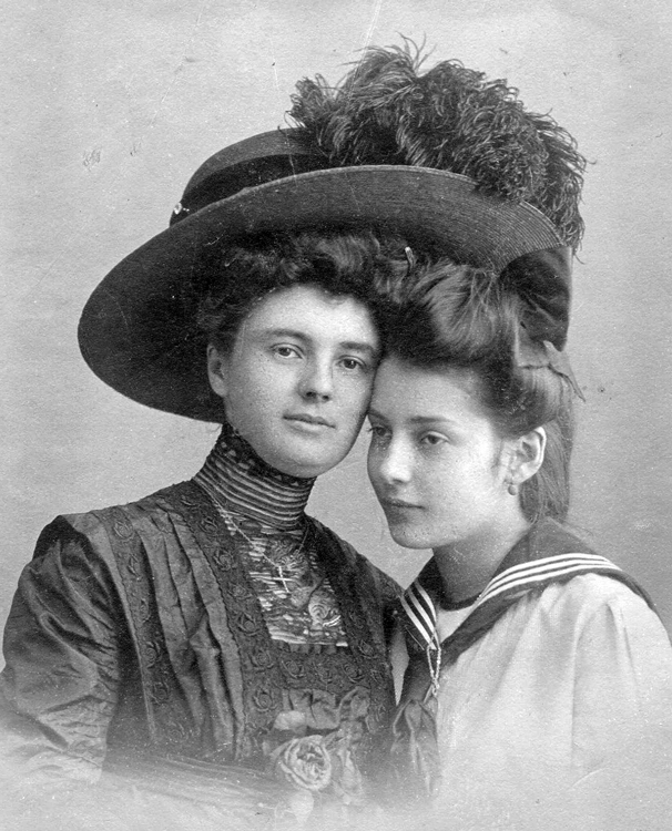 Two women in the 1900s, one wearing a large Edwardian style hat