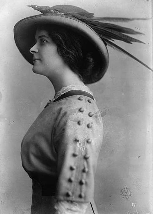woman in true 1910s fashion wearing a large, embellished hat