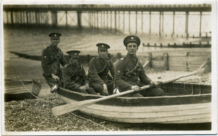World War 1 soldiers in a row boat on the shore.