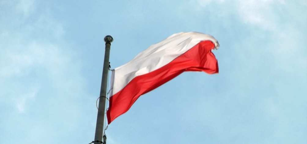 The flag of Poland flying in front of the blue sky.