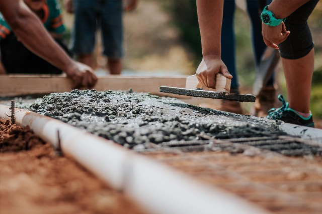 People working with concrete to build a home
