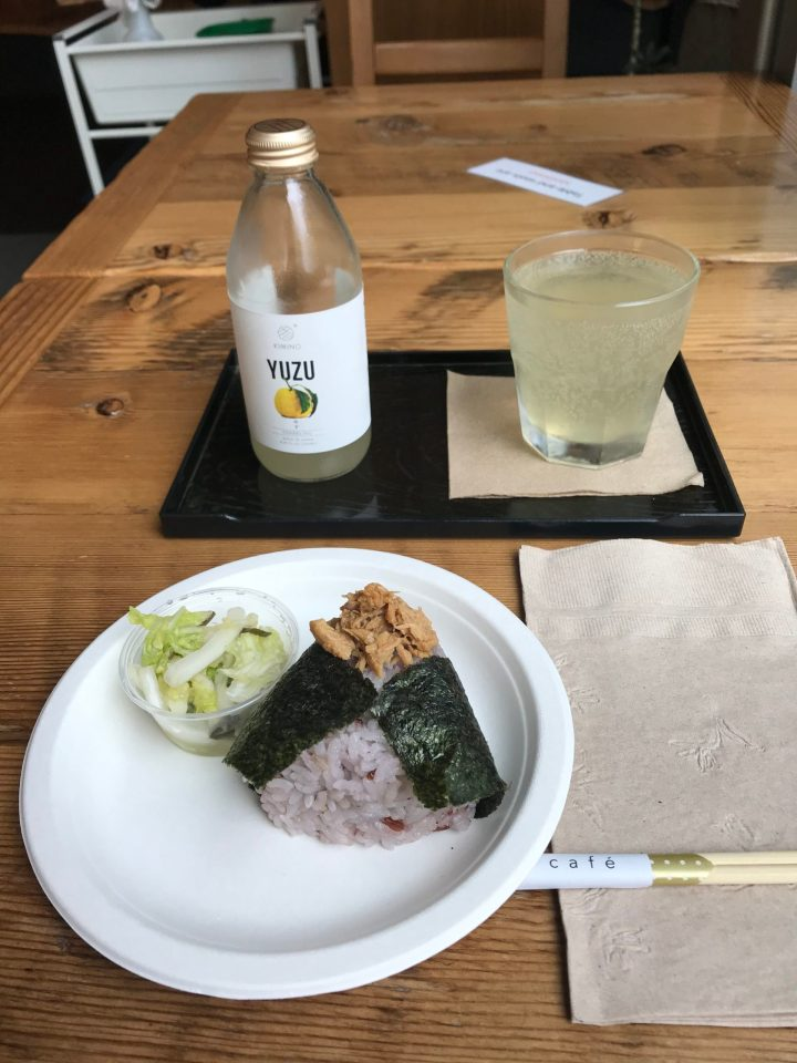 Photo of a glass of sparkling yuzu and chicken teriyaki onigiri.