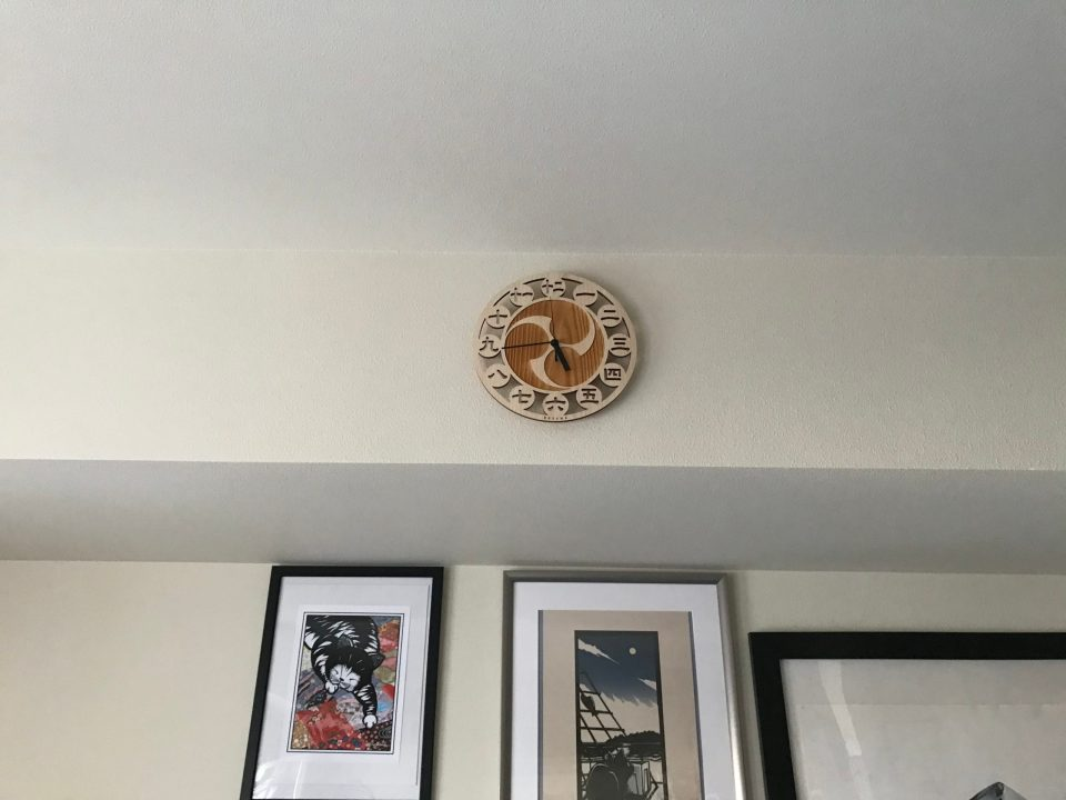 Photo of a wooden clock mounted to a wall.