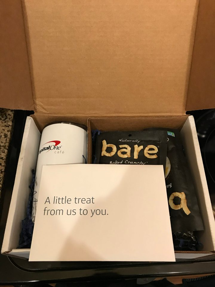 Photo of a box of snacks and a coffee tumbler from Capital One Cafe.