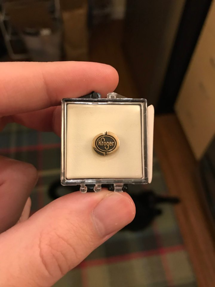 Photo of a gold Kroger pin in a case.