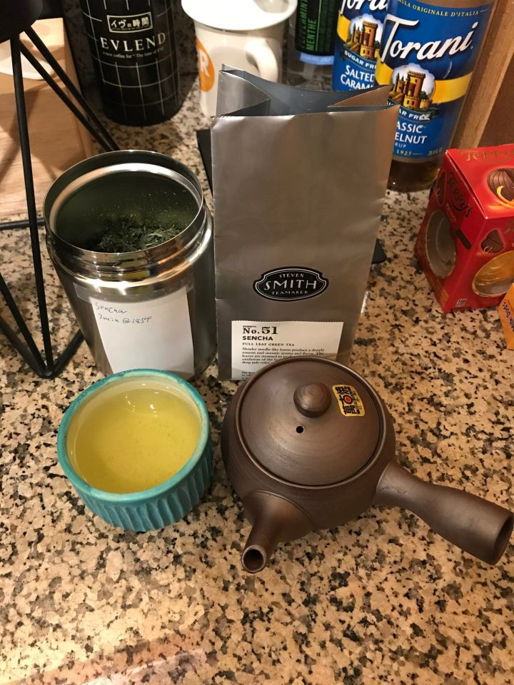 Photo of a cup of Sencha with teapot and canister of leaves.