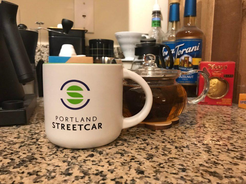 Photo of a Portland Streetcar mug next to a tea pot.
