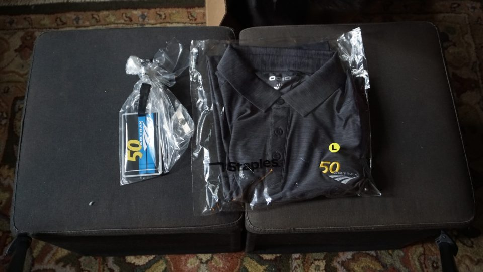 Photo of an Amtrak 50th anniversary polo and luggage tag.