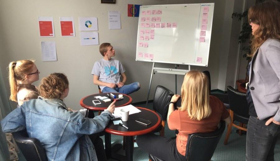 Rektor Ann Birgitte Tveiten ser på mens en av gruppene jobber med ideer til deres svar på 24-timers oppgaven de har fått