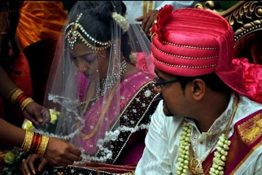 Bridesmaid adjusts bride's veil