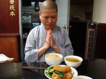 Buddhist man prays before eating a meal prepared at his temple. Photo by Ramaa Raghavan