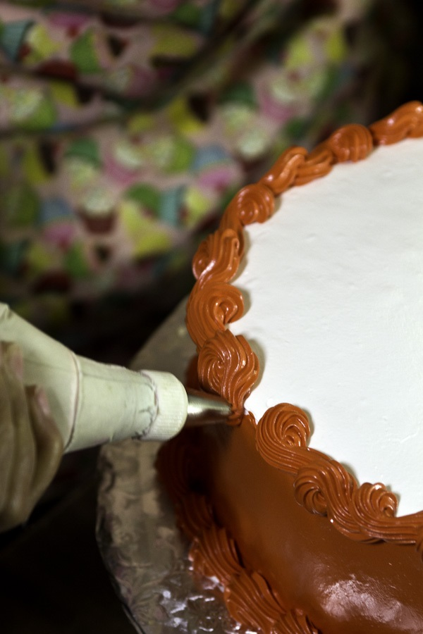Then Andujar covers the whole cake with a thick layer of white suspiro and dyes another batch bright red. She layers the red over the white so she doesn't have to use as much dye, which she says can give the cake a bitter taste.