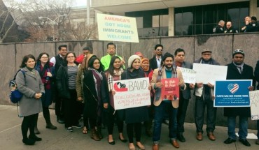A group of Desi-American activists don signs of welcome to immigrants
