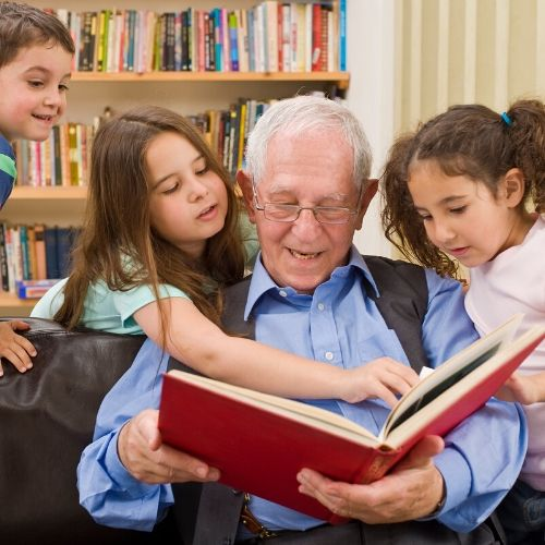 Shows Grandpa enjoying a personalized book with grandchildren