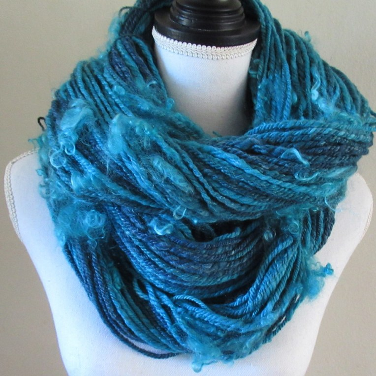 Turquoise yarn worn like a cowl