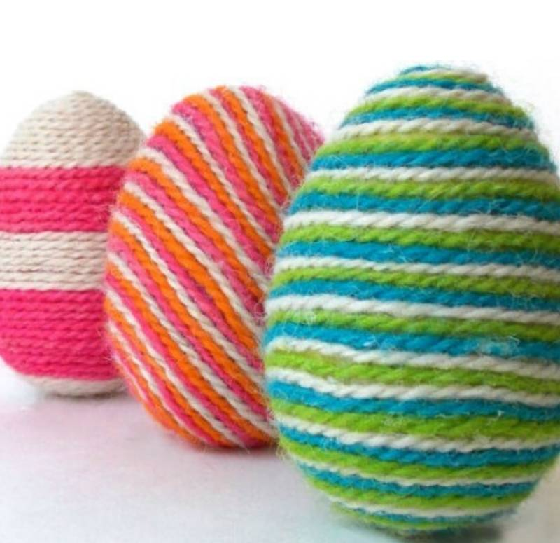 Decorating Easter Eggs with colorful yarn