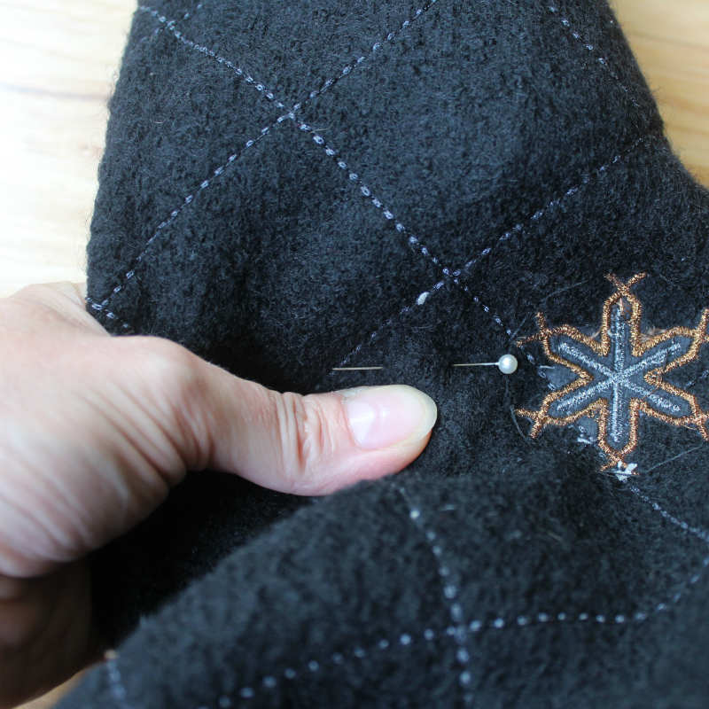 Place a pin on the seam line of the sweater sleeve