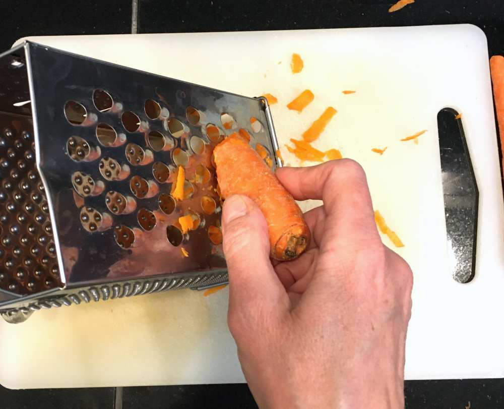 Grating carrots to make orange