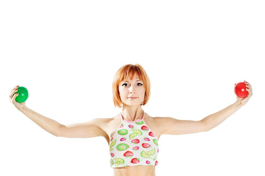Das Bild zeigt ein Foto von einer Frau vom Bauch aufwärts. Sie trägt ein Top mit aufgedrucktem Obst. Sie hält ihre beiden Arme waagerecht von sich. In der einen Hand hält sie einen roten, in der anderen einen grünen Ball. Sie hat rote kinnlange Haare. Das Bild soll Stärke, Mut und Balance ausstrahlen.