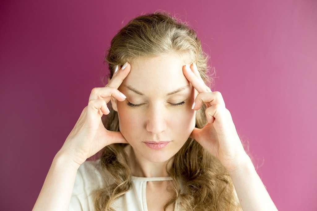 Das Bild zeigt eine Junge Frau mit geschlossenen Augen, die sich mit beiden Händen an die Stirn greift. Sie trägt eine Weise Bluse und sie hat lockige helle Haare. Zu sehen ist lediglich ihr Oberkörper und im Hintergrund ist eine dunkelrosa Wand zu sehen. Symbolbild für den Umgang mit Fibromyalgie und andere unsichtbare Erkrankungen