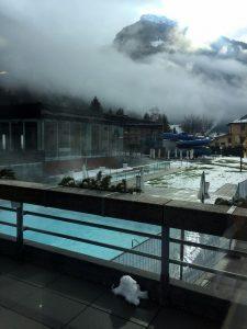 Das Bild zeigt das Außenbecken der Felsentherme Bad Gastein. Im Vordergrund ist ein Geländer zu sehen. Im Hintergrund ein Wolkenverhangener Berghang. Vom Beckenwasser steigt Dampf aus.