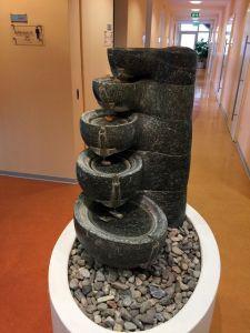 Das Bild zeigt einen Brunnen im Kurhaus. Er besteht aus grauem Stein. Fünf runde Becken sind stufenförmig übereinander angeordnet.