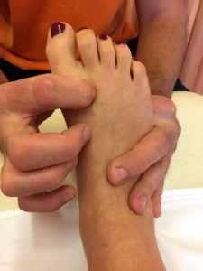 Das Bild zeigt einen Fuß in Großaufnahme. Die Nägel sind rot lackiert und ein Therapeut legt beide Hände an den Fuß.