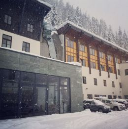 Das Bild zeigt das Kurhaus des Gasteiner Heilstollens im Schnee. Vorne ist die Glasfront des Bistros zu sehen und ein paar parkende Autos. Darüber sieht man drei weitere Stockwerke und dahinter den Berghang mit verschneiten Nadelbäumen.