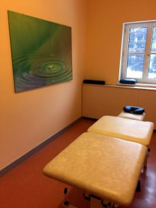Das Bild zeigt einen kleinen Raum, in dem Boden und Wände orange sind. Im Raum steht eine Massageliege. An der Wand hängt ein großes Foto, das eine Wasseroberfläche zeigt. Am Ende des Raumes sieht man durch das Fenster einen verschneiten Berghang.