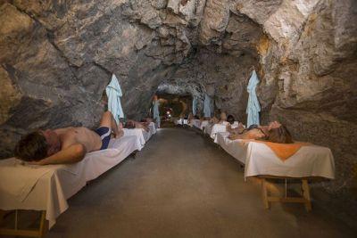 Zu sehen ist ein langer Gang, der in das Berggestein gehauen wurde. Rechts und links stehen hölzerne Liegen am Gang entlang, auf denen Menschen in Badekleidung liegen.
