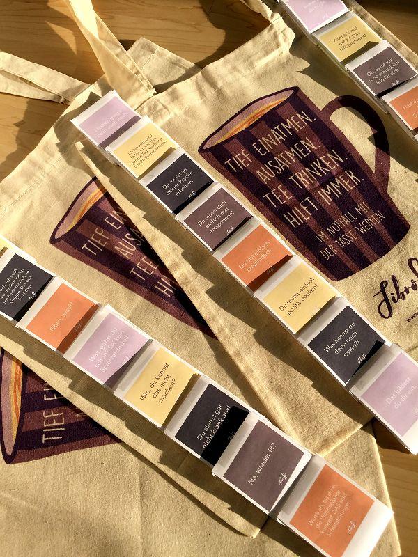 """Das Bild zeigt mehrere Stofftaschen, die auf Holzboden liegen. Auf den Taschen liegen kleine Briefchen, auf denen jeweils ein Spruch aus FibroFees Bullshit-Bingo aufgedruckt ist. . Auf der Tasche ist eine lila Tasse aufgedruckt, auf der steht: """"Tief einatmen. Ausatmen. Tee trinken. Hilft immer. Im Notfall mit der Tasse werfen."""" Darunter ist das FibroFee-Logo und die Webadresse aufgedruckt."""